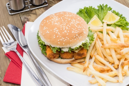 Heap of Chips with Fish Burger on wooden background photo