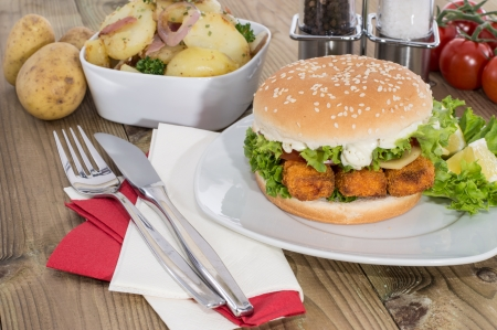 Fish Burger with fried Potatoes in a bowl on wooden background photo