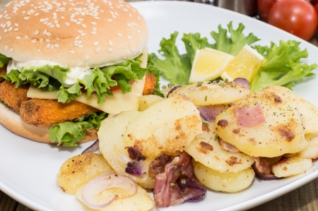 Fish Burger with fried Potatoes on wooden background photo
