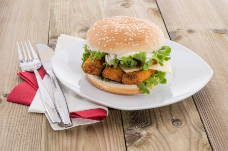 Fish Burger on a plate on wooden background photo