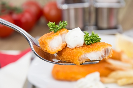 fried snack: Pieces of fried Fish on a fork with lunch in the background Stock Photo