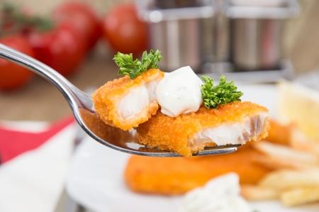 fish and chips: Trozos de pescado frito en un tenedor con la comida en el fondo Foto de archivo