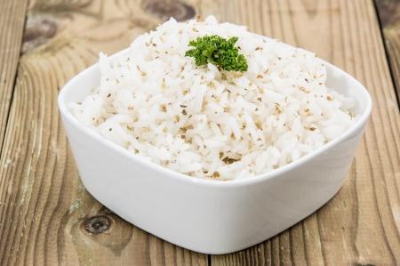 arroz chino: Arroz dulce cocido en un plato sobre fondo de madera
