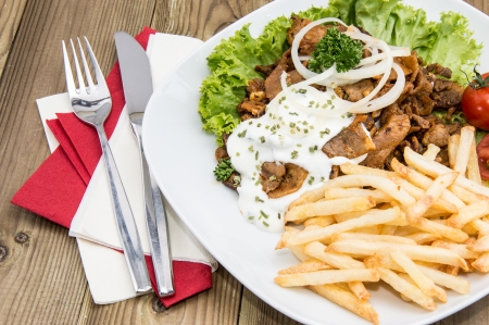 Plate with Chips and fresh Kebab on wooden background
