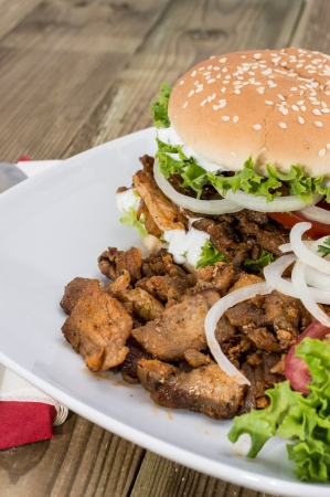 Fresh homemade Kebab Burger with Chips on wooden background photo