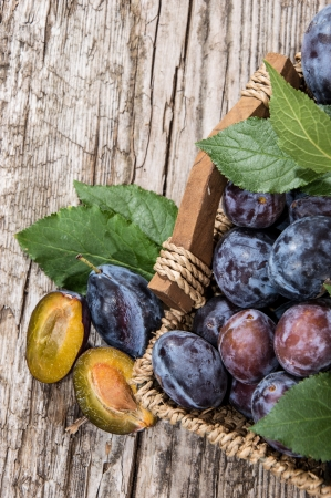 Basket filled with fresh Plums and leaves on wooden background photo