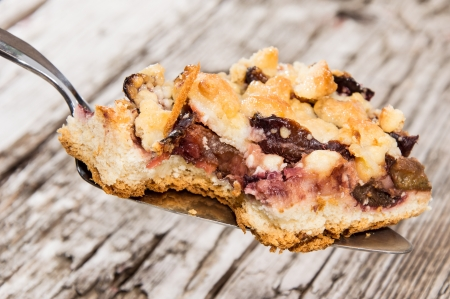 Piece of Plum Cake on a lifter against wooden background photo