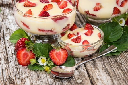 Bowls with Vanilla Pudding and fresh Fruits on wooden background photo