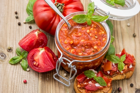Bruschetta Sauce (in a glass) against wooden background photo