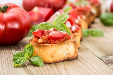 Fresh made Antipasti (Bruschetta) on wooden background