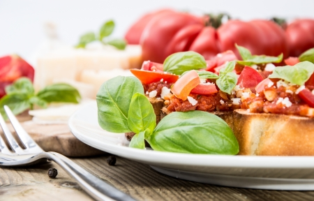 Bruschetta on a plate (macro shot) against wooden background photo