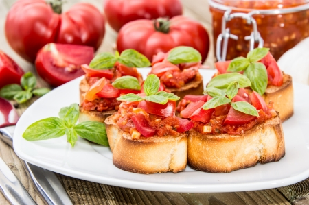 Bruschetta with ingredients in the background  photo