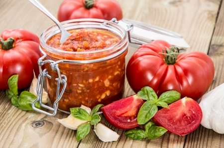 Tomato Sauce in a glass with ingredients against wooden background photo