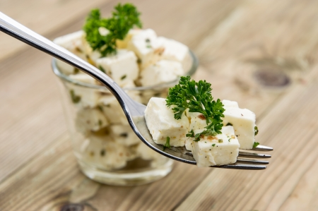 Feta Cheese Cubes on a fork with ingredients in the background photo