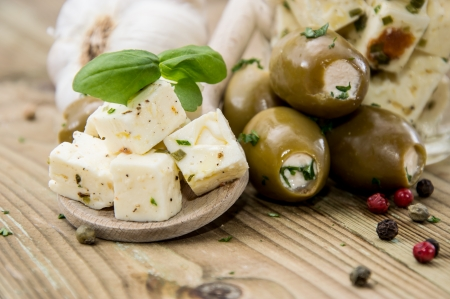 cottage cheese: Wooden spoon with Feta and Olives against wooden background Stock Photo