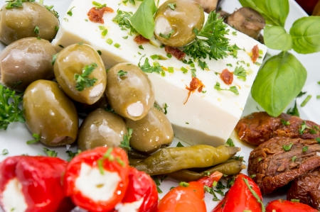 Different types of Antipasto on a plate against wood photo