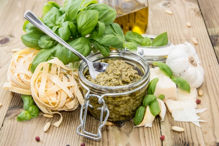 Pesto Sauce in a Glass on wooden background photo
