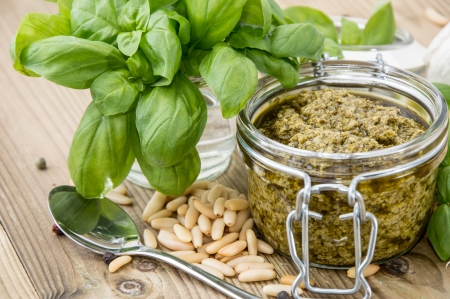 Pesto Sauce in a Glass on wooden background