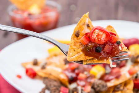 Fresh Nachos on a fork with portion in the background photo