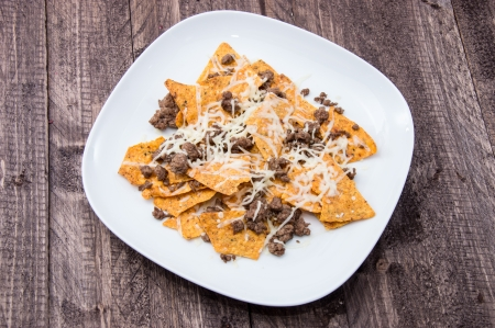 Plate with Portion of fresh Nachos on wooden background photo