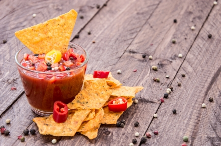 Glass with Salsa Sauce and Nachos on wooden background photo