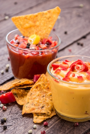 Salsa- and Cheese Sauce with fresh Nachos on wooden background photo