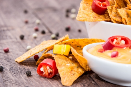 Bowl with Nachos and Cheese Sauce on wooden background photo