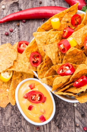 Bowl with Nachos and Cheese Sauce on wooden background Stock Photo - 15220497