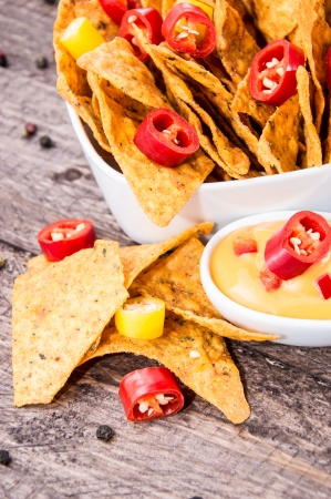 Portion of Nachos with Cheese Sauce on wooden background photo