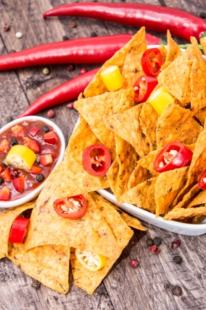 Portion of Nachos with Salsa Sauce on wooden background photo