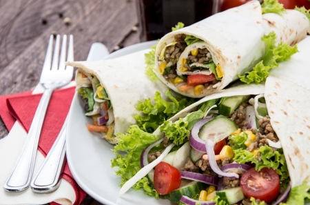 Heap of Wraps on a plate against wooden background photo