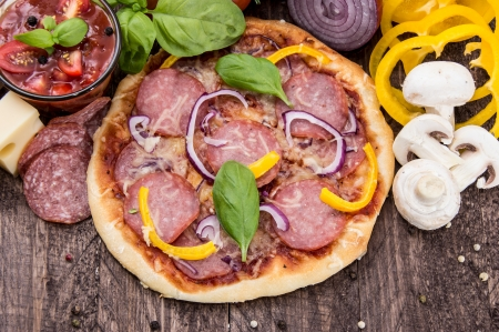 Fresh made Salami Pizza on wooden background photo