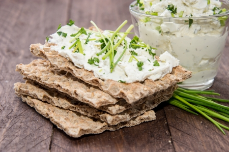 crispbread: Pane croccante, crema Chesse ed erba cipollina su sfondo in legno