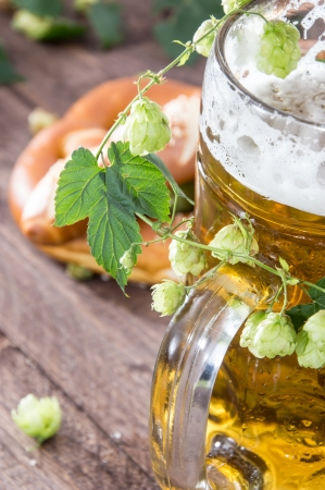 Mug of Beer with hop (macro shot) on wooden background photo