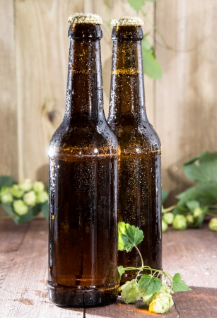 Two wet bottles of Beer decorated with Hops on wooden background photo