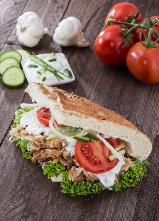Kebab and Pita with ingredients on wooden background Imagens