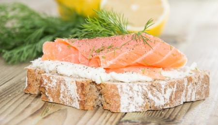 Salmon on a bread with horseradish on wooden background photo