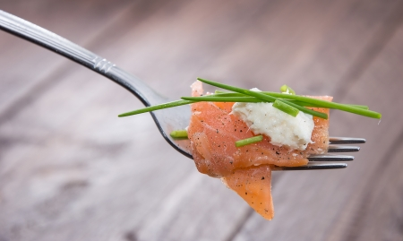 Piece of Salmon on a fork on wooden background photo