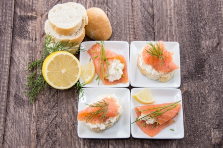 Salmon starters on small plates against wooden background photo