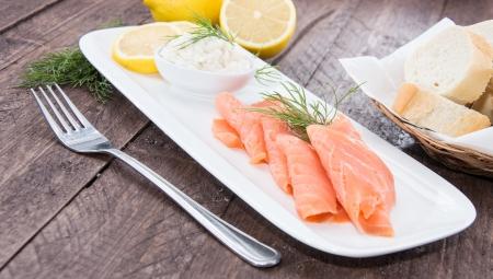 salmon ahumado: Placa con salmón sobre fondo de madera