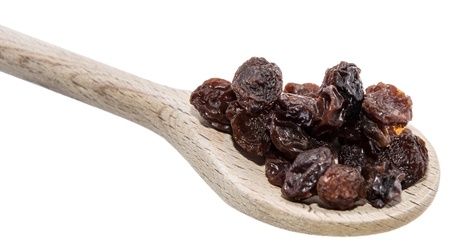 Raisins on a wooden spoon against white background photo