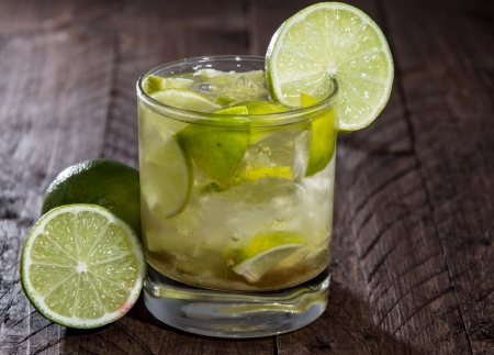 caipirinha: Glass with Caipirinha on wooden background