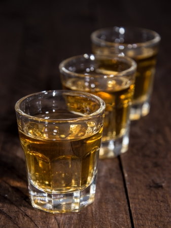 Rum Shots in a line on wooden background photo