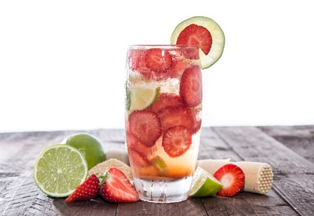 Strawberry Caipirinha on a wooden Table against white background photo