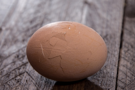 broken egg: Cracked egg on wooden background Stock Photo