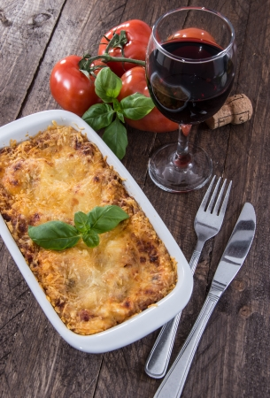 Baking dish with Lasagne on wooden background photo