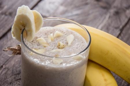 licuado de platano: Fresh pl�tano Milkshake hecho en el fondo de madera