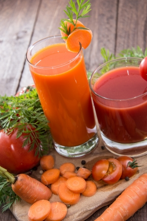 jugo de tomate: Zanahoria y jugo de tomate con trozos frescos de ingredientes Foto de archivo