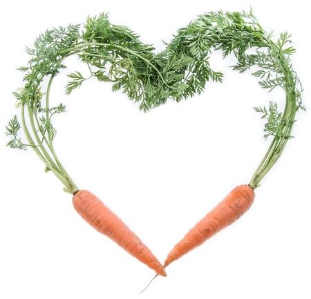 zanahoria: Zanahorias frescas que dan forma un coraz�n aislado en blanco Foto de archivo