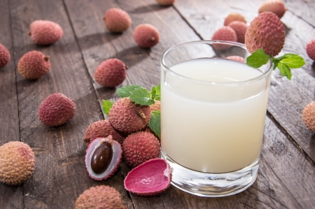 litschi: Fresh made Lychee Juice on wooden background Stock Photo